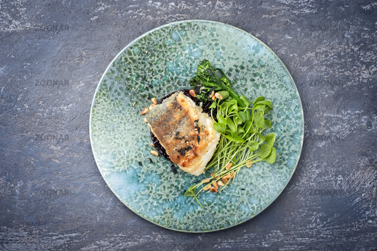 Modern style traditional pan-fried skrei cod fish filet in breadcrumbs with baby broccoli