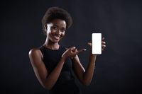 Smiling black woman pointing with finger on empty template mobile phone white screen