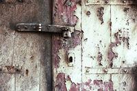 rusty door lock with bolt on weathered wooden door