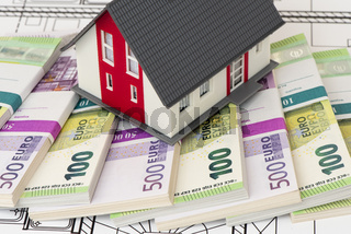 Euro banknotes laying under model home