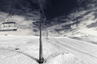 Snowy ski slope, chair-lift on ski resort and sky with clouds. Black and white retro toned landscape.