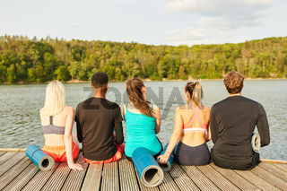 Freunde sitzen nach einem Fitness Kurs am See