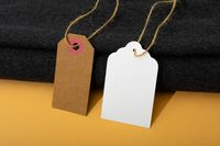Composition of gift tags with copy space and black fabric on yellow background