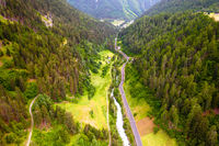Stelvio pass road and river canyon in Dolomites Alps aerial view