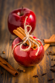 Organic red apples with cinnamon stick and cloves as baking ingredients on wooden background