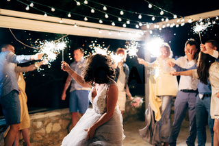 Budva, Montenegro - 21 august 2020: bride dancing among guests with sparklers at the wedding party