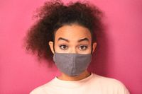 Recognize emotions in a reusable mask during quarantine African American girl in peachy t-shirt, to prevent others from corona COVID-19 and SARS cov 2 infection isolated on pink background