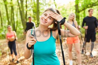 Schwitzende junge Frau nach Nordic Walking Kurs
