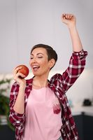 Holding an apple in hand happy woman dancing at kitchen with a sexy eye contact on camera. Charming housewife wearing plaid shirt with a short hair while cooking apple pie standing at the kitchen