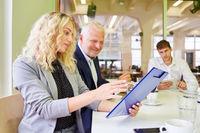 Geschäftsfrau mit Klemmbrett und Manager im Meeting