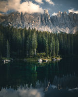 The Latemar mt and a wood reflected in the lake Karersee in a cloudy day at sunset, Dolomites, Italy