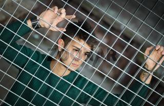 Attractive young man behind metal or steel net