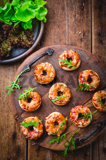 Small pizza in donut shape with rocket (arugula) and fresh salad on wooden background