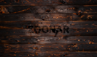 Burnt wooden board, black charcoal wood texture, burned barbecue background