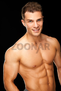 Handsome muscular young man isolated on black