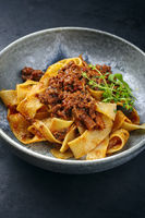Modern style traditional Italian ragu alla bolognese sauce with papedelle pasta noodles and parmesan cheese served as close-up in a ceramic design bowl