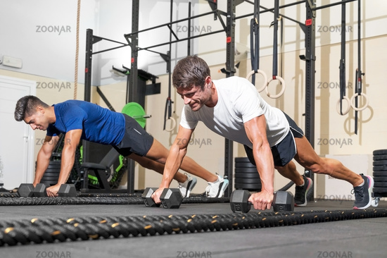Two strong men doing push-ups in gym.