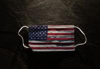Surgical American flag facemask on dark background --  USA Coronavirus concept