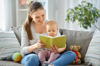 happy mother reading book to little baby at home