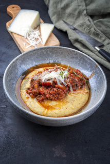 Modern style traditional Italian polenta alla sarda con salsiccia with ground meat ragu and pecorino served as close-up on a Nordic design bowl
