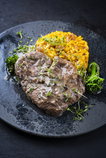 Modern style traditional braised Italian ossobuco alla Milanese with saffron risotto and baby broccoli in white wine meat sauce served on a Nordic design plate with copy space
