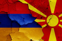 flags of Armenia and North Macedonia painted on cracked wall