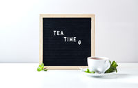 Tea time. Black letter board with text on table with glass cup of tea with mint leaves