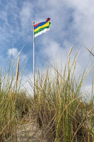 Flag of Terschelling on a dune against a blue sky with white clouds