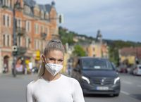 young blond woman with mask in the city