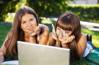 Happy young student girls using a computer outdoors