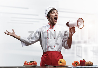 Young chef shouting loudly into megaphone
