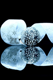metallene christbaumkugel vor blauem band
