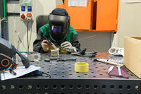 A woman employed in a modern factory for the production and processing of metals in a work uniform welds metal materials