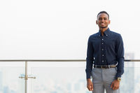 Handsome African businessman outdoors at rooftop smiling