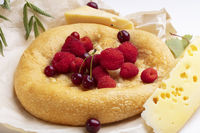 Lavash with red berries and a piece of cheese. Baked round bun for breakfast.