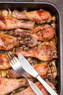 baked chicken legs in tray on black wooden