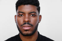 Focused millennial African American young serious black man looks at the camera.