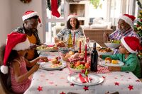Happy multi generation family wearing santa hats, having christmas meal