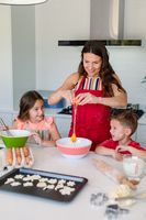 Happy caucasian mother, daughter and son baking together, making cookies in kitchen