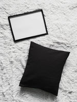 Thin wooden frame with blank copyspace as poster photo print mockup, black cushion pillow and fluffy white blanket, flat lay background and art product