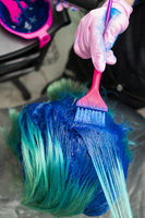 Hairdresser in protective glove using pink brush while applying blue paint to customer during process of dyeing hair in stylish color