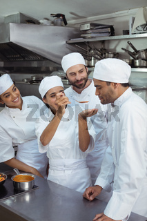 Chef tasting food to colleague in kitchen