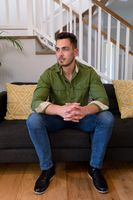 Thoughtful caucasian man sitting on sofa and looking at camera