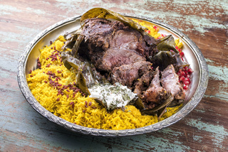 Slow cooked Omani lamb shuwa coated in rub of spices and wrapped in banana leaves served with rice and yoghurt as close-up on a rustic oriental tray