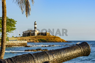 Old cannon and the Barra Lighthouse (Farol da Barra)  in the city of Salvador in Bahia surrounded by the sea