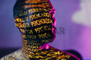 Young adult man with words Psychology on his face in the dark.