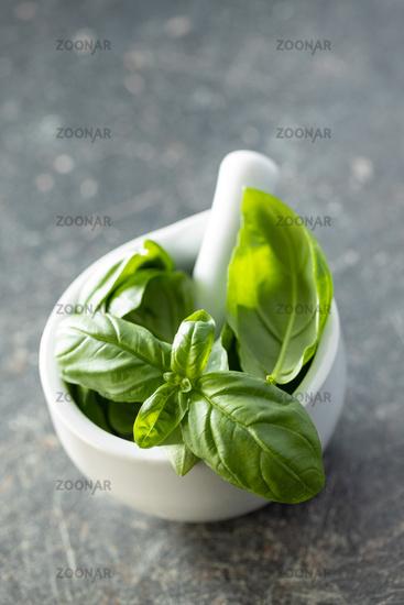 Fresh green basil leaves in mortar.