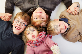 Vier Geschwister liegen im Kreis