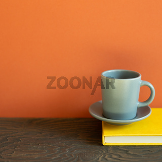 Yellow diary note book with cup of coffee on wooden desk. red wall background