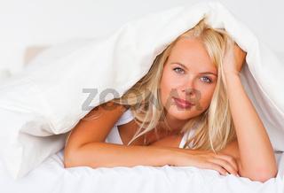 Blonde woman under a duvet